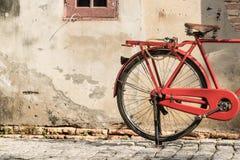 在老城市墙壁旁边的红色自行车 图库摄影