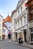 在老城市的街道上的游人2012年6月16日的在塔林,爱沙尼亚 库存图片