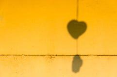 在老墙壁上的心形的阴影 库存照片