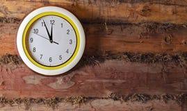 在老墙壁上的时钟由日志做成 库存图片