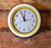 在老墙壁上的时钟由日志做成 库存照片