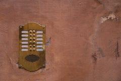 在老墙壁上的老古铜色对讲机有削皮油漆的 免版税库存照片