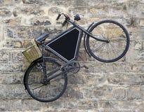 在老墙壁上的葡萄酒自行车 库存照片