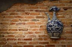 在老墙壁上的陶瓷瓶 免版税库存图片
