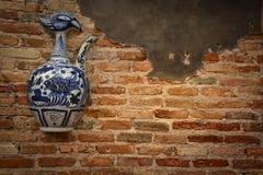 在老墙壁上的陶瓷瓶 图库摄影