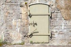 在老墙壁,背景纹理的绿色金属门 免版税库存照片
