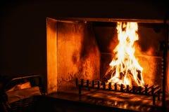 在老壁炉的火在暗室 库存图片