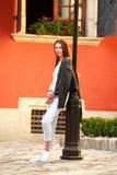 在老夏天游人镇街道上的青少年的女孩  免版税图库摄影