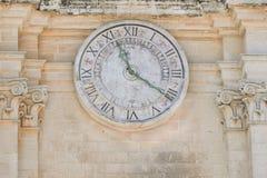 在老大厦的古代人时钟 免版税图库摄影