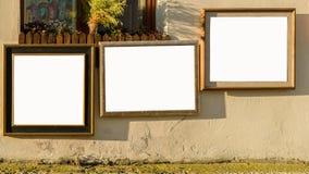 在老大厦门面的三个图片木制框架在期间 免版税库存照片