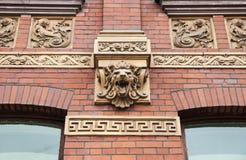 在老大厦门面的狮子头 免版税库存图片