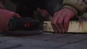 在老夹克的人的手使用机械螺丝刀连接板条 股票录像