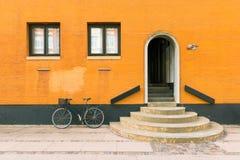 在老居民住房的橙黄色的墙壁的附近黑自行车在哥本哈根,丹麦 库存照片