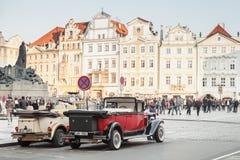 在老布拉格街道上的红色老朋友汽车  免版税库存照片