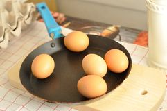在老平底锅的未加工的鸡蛋在木头 库存照片