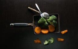 在老平底锅的硬花甘蓝和红萝卜食物样式在黑木桌上 免版税图库摄影
