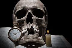 在老开放书的人的头骨与在黑背景的灼烧的蜡烛和葡萄酒时钟在光柱关闭下 库存照片