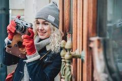 在老影片照相机的年轻白肤金发的卷曲女性射击照片 图库摄影