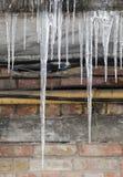 在老房子的冰柱在冬天 免版税库存图片