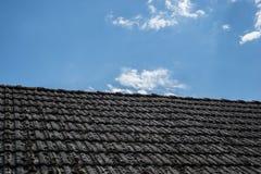 在老房子的年迈的瓦在村庄 在小屋铺磁砖的屋顶的很多青苔反对蓝色多云天空的 蓝色乡下空的路场面天空 免版税库存照片