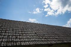 在老房子的年迈的瓦在村庄 在小屋铺磁砖的屋顶的很多青苔反对蓝色多云天空的 蓝色乡下空的路场面天空 库存照片