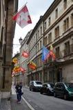 在老房子窗口的瑞士国民和城市旗子 库存图片