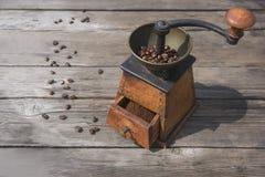 在老手工研磨机的咖啡豆在木桌上 库存图片