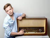在老收音机附近的男孩少年 免版税库存照片