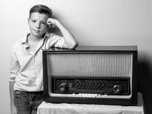 在老收音机附近的男孩少年 免版税库存图片