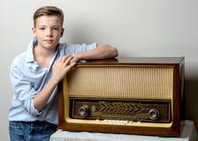 在老收音机附近的男孩少年 库存图片