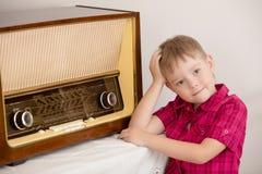 在老收音机附近的男孩 免版税库存图片
