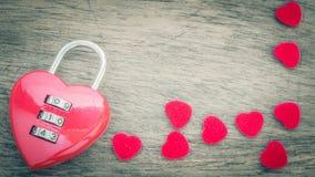 在老木书桌上的红色关键心脏形状 库存照片