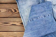 在老木土气棕色桌上的蓝色牛仔裤 库存图片