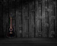 在老木墙壁上的吉他。 免版税图库摄影