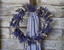 在老木墙壁上的淡紫色花圈 库存图片
