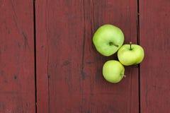 在老木桌上的三个绿色苹果 免版税库存照片