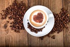 在老木桌上的咖啡杯热奶咖啡 心脏形状泡沫,顶视图 库存照片