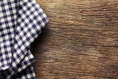 在老木桌上的方格的餐巾 库存照片