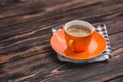 在老木桌上的橙色咖啡杯 免版税库存照片