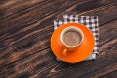 在老木桌上的橙色咖啡杯 免版税库存图片