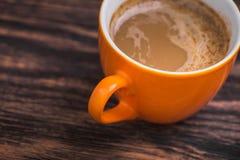 在老木桌上的橙色咖啡杯 库存照片
