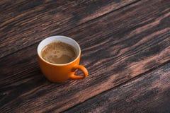 在老木桌上的橙色咖啡杯 库存图片