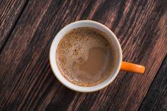 在老木桌上的橙色咖啡杯 图库摄影