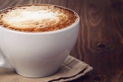 在老木桌上的热奶咖啡 免版税库存图片