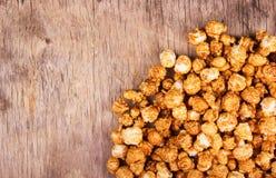 在老木桌上的焦糖玉米花 驱散在木背景的甜玉米 快餐 有害和可口食物 免版税库存图片