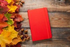 在老木桌上的红色笔记薄 混杂的槭树秋叶和橡子在一个闭合的笔记本旁边 免版税图库摄影