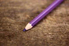 在老木桌上的紫色铅笔 库存图片