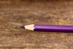 在老木桌上的紫色铅笔 免版税库存照片