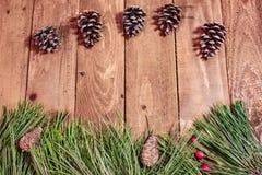 在老木桌红色berrys和云杉的Xmas背景 免版税库存图片
