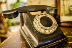 在老木桌背景的残破的葡萄酒黑色电话 免版税图库摄影